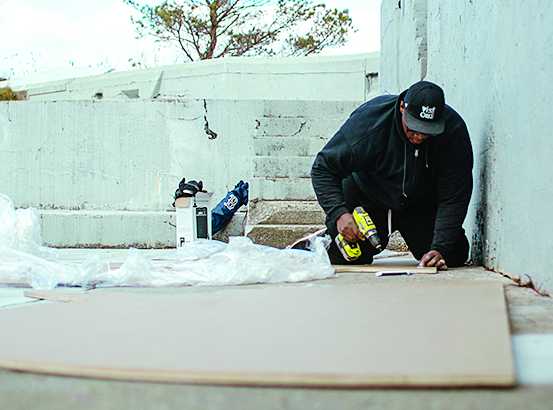 man on hands and knees with drill building a wedding proposal sign for his girlfriend