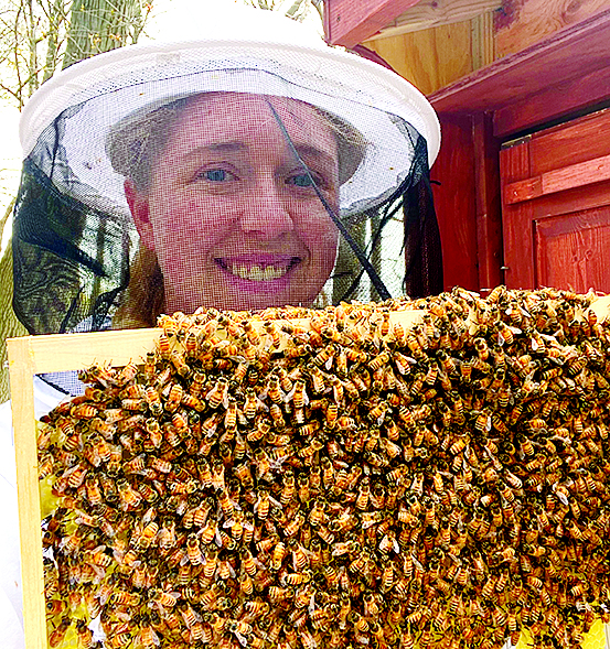 lady standing in front of bee hive