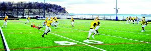 teenagers playing football on green field in practice uniforms next to ocean in hull massachusetts