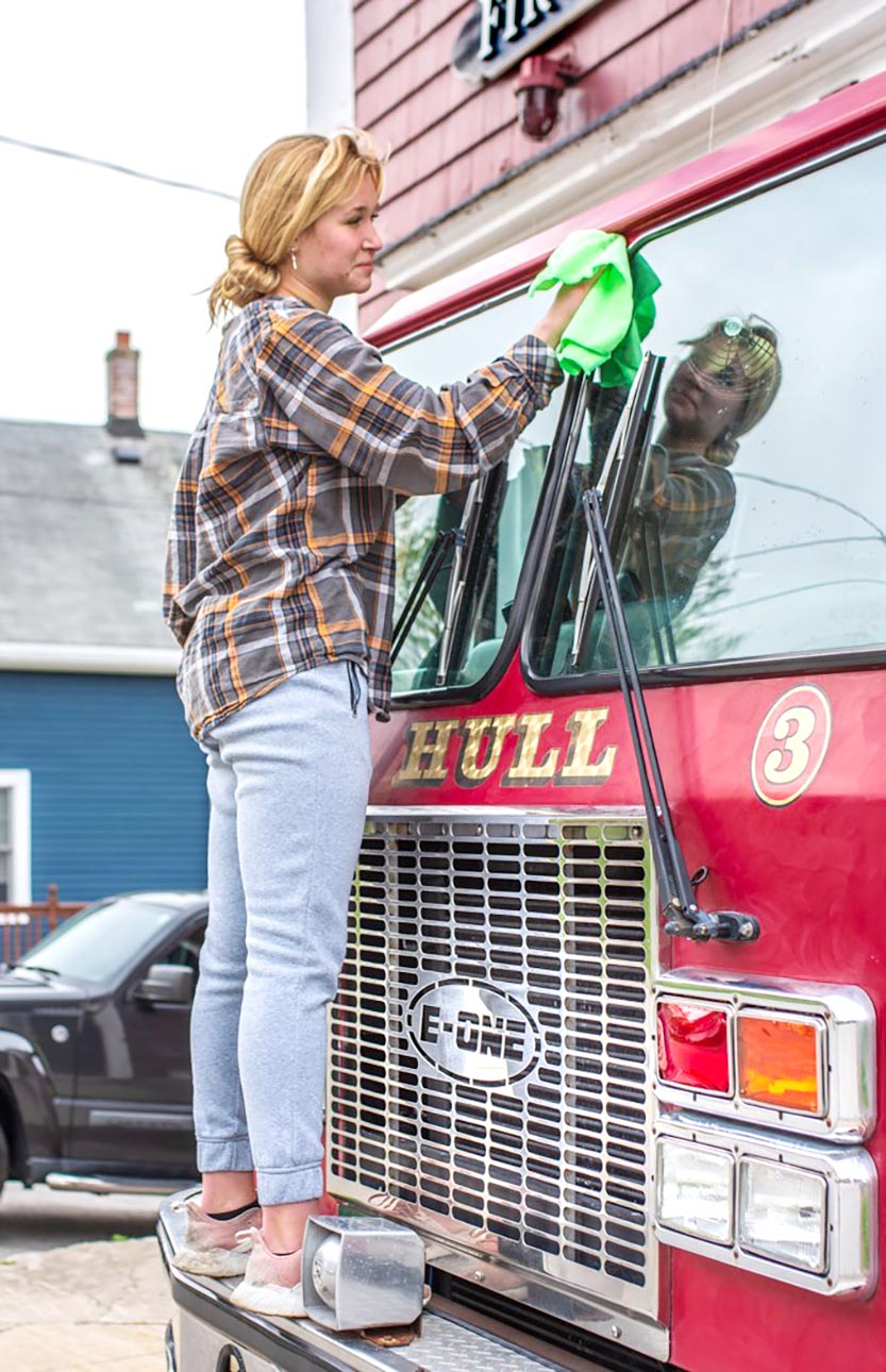 young lady cleaning a red fire truck glass window, standing on front bumper