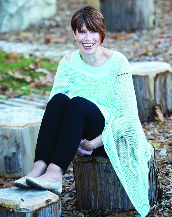 lady sitting on a wood stump wearing a mint covered cardigan