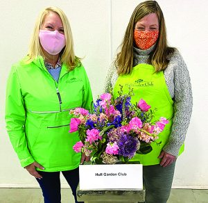 TWO LADIES WEARing green standing in front of bouquet and a sign saying hull garden club