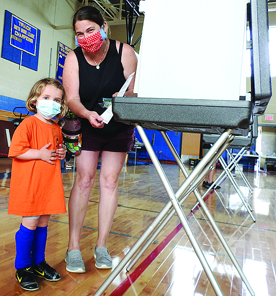 mother and child voting inside high school gymnasium