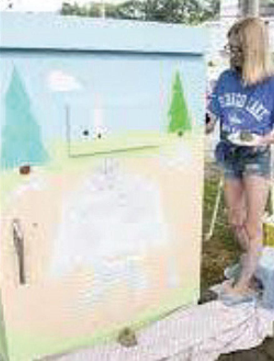 person painting grass and tree scene on a utility box