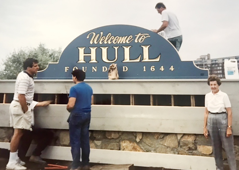 people standing in front of hull garden club sign