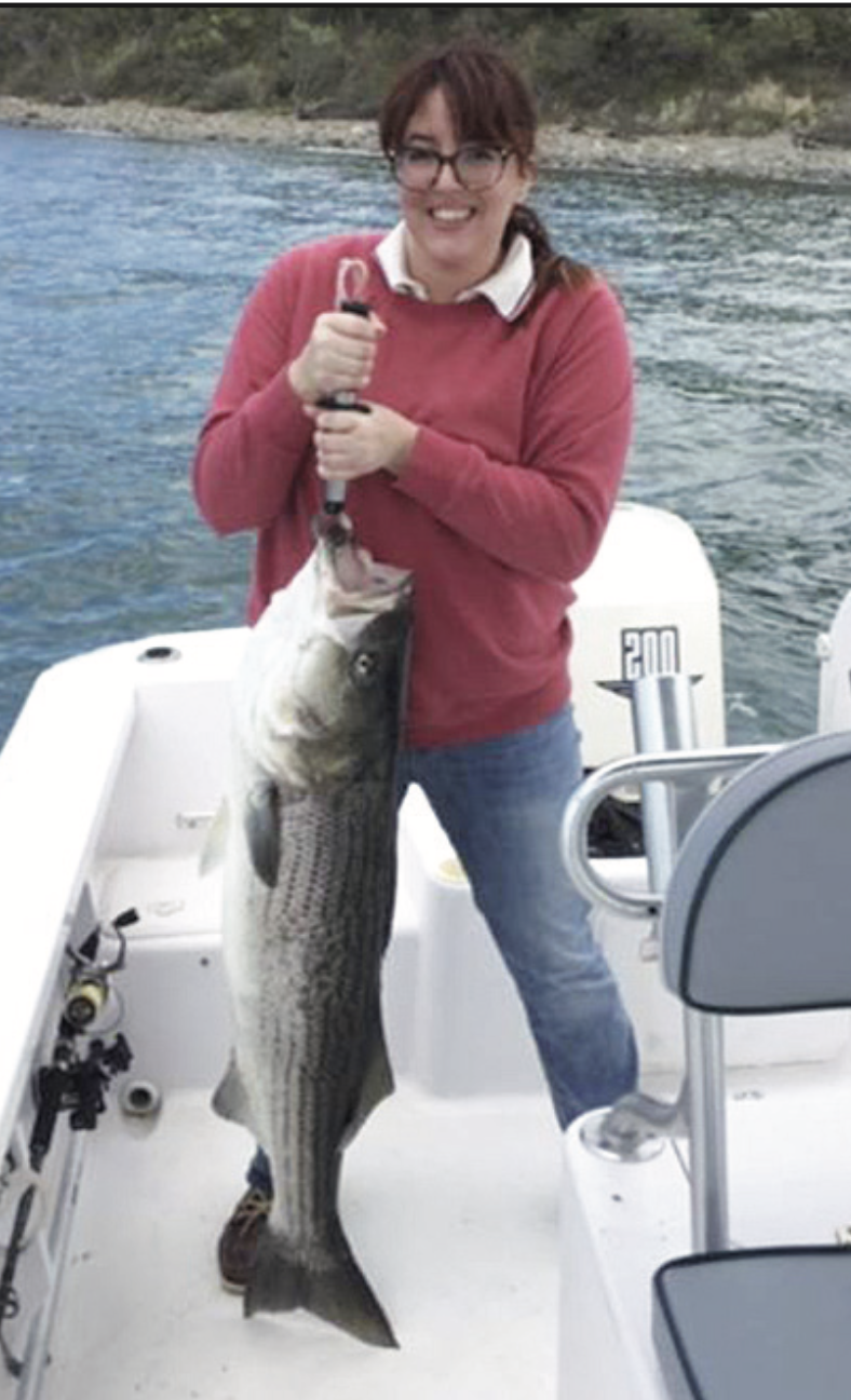 lady holding large fish on hook that she recently caught